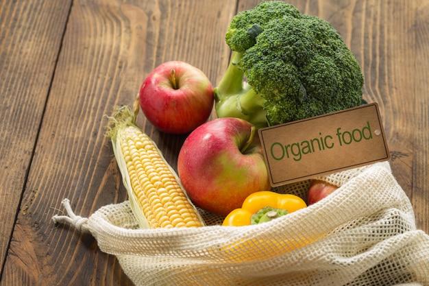 Biologisch voedsel concept. volledige netwerkzak verschillende natuurlijke voeding op houten lijst