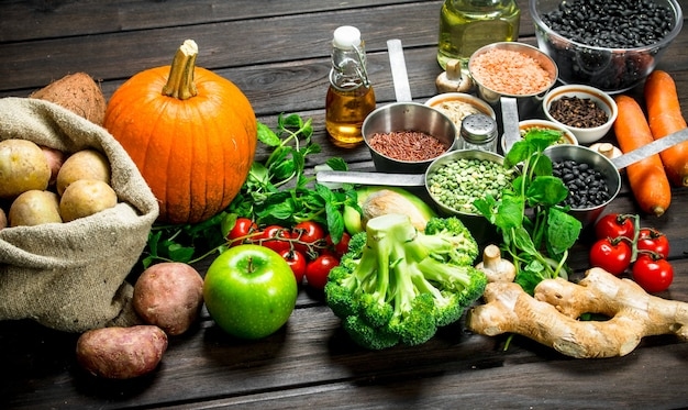 Biologisch voedsel. gezond assortiment van groenten en fruit met peulvruchten op een houten tafel.