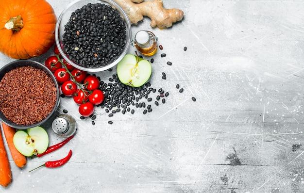 Biologisch voedsel. gezond assortiment van groenten en fruit met peulvruchten op een rustieke tafel.