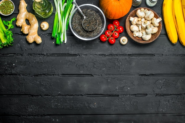 Biologisch voedsel. gezonde groenten en champignons met bonengranen. op een zwarte rustieke tafel.