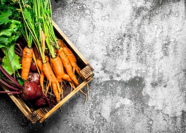 Biologisch voedsel. groenten in een oude doos. op een rustieke achtergrond.