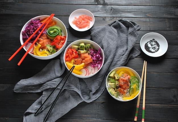 Biologisch voedsel. recept voor verse zeevruchten. de verse zalm porren kom met rijst, verse rode kool, avocado, kersentomaten, komkommer, radijsspruiten op houten achtergrond. food concept zakje