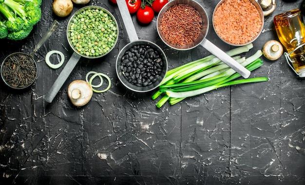 Biologisch voedsel. verschillende gezonde groenten en fruit met bonen op een zwarte rustieke tafel.