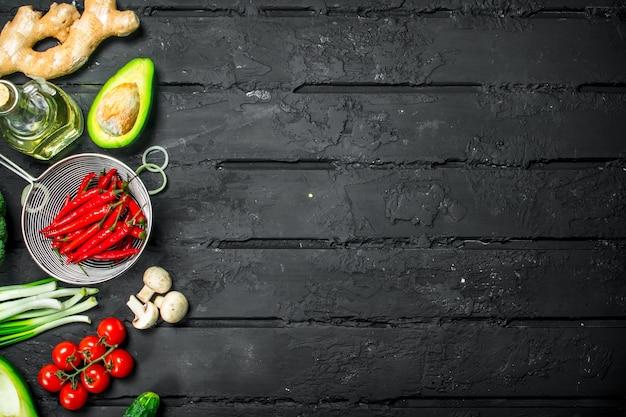 Biologisch voedsel. verschillende gezonde groenten. op een zwarte rustieke tafel.