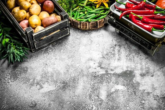 Biologisch voedsel. verse groenten in een doos en spaanse peperpeper op schalen. op een rustieke achtergrond.