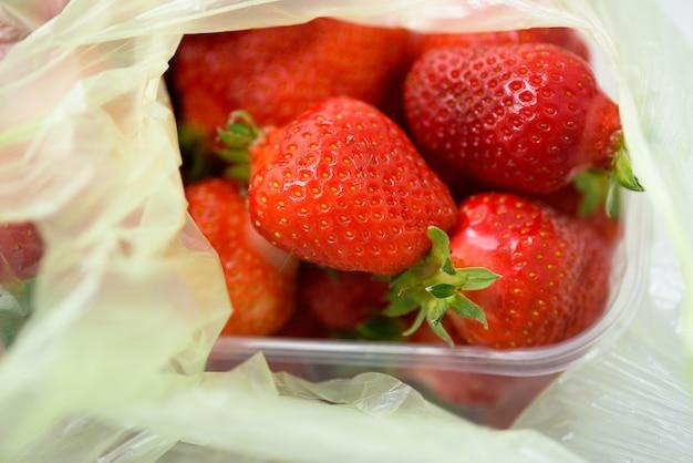 Biologische aardbeien in een plastic doos en zakken. levering van biologische producten.