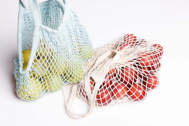 Biologische appels in rieten tas om te winkelen op een witte achtergrond, eco boodschappentas concept. geen afvalconcept met kopieerruimte, plasticvrij concept