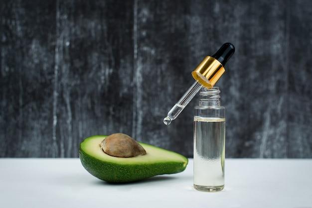 Biologische avocado-olie in een fles met een pipet op een zwart-wit houten