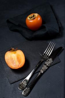 Biologische bio persimmon op zwart.