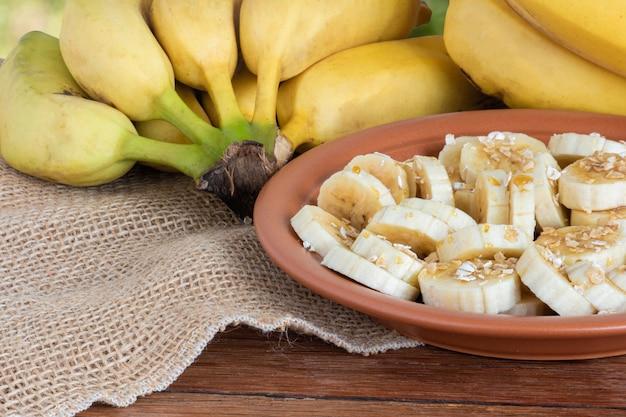 Biologische bos rijpe gele bananen. stukjes gesneden op een bord met honing en haver.
