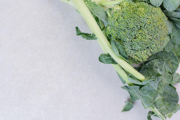 Biologische broccoli met bladeren op witte tafel.