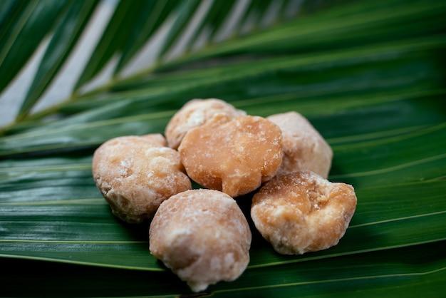 Biologische bruine palmsuiker of kokossuiker op groene kokosblaadjes. zoete suiker gemaakt van kokosbloem