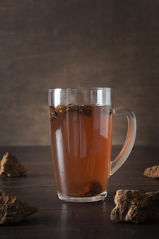 Biologische chaga paddestoelen warme koffie in glazen beker. trendy gezonde schoon eten drank op donker.