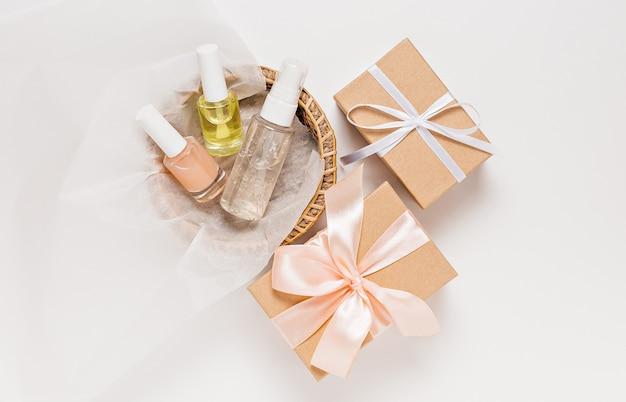 Biologische cosmetica en cadeaus voor de vakantie. platliggend, bovenaanzicht helder glazen pompflesje, penseelpotje, vochtinbrengende serumpotje in een papieren mandje op een witte achtergrond. natuurlijke cosmetica spa