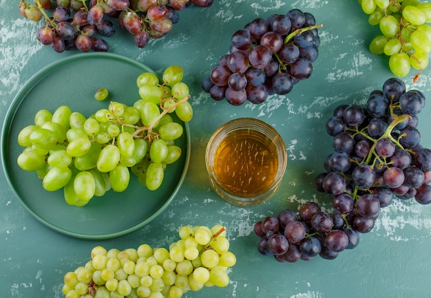 Biologische druiven met drankje in een dienblad op gips achtergrond, bovenaanzicht.