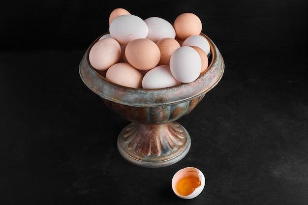 Biologische eieren en eierschalen in een metalen kom op zwarte ondergrond.