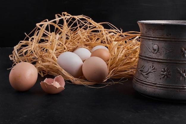 Biologische eieren in het nest op zwarte ruimte.