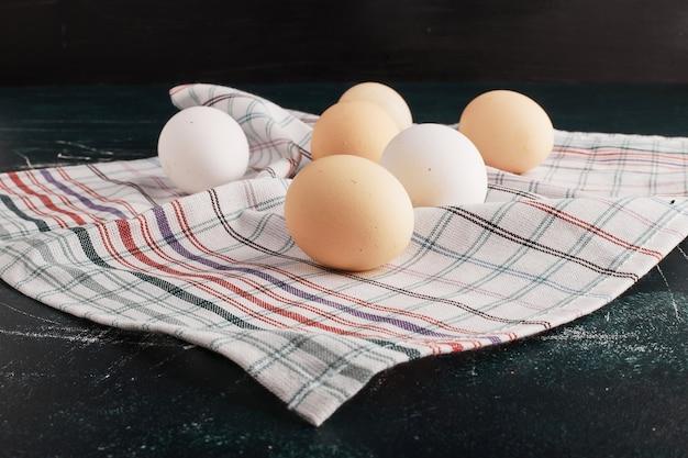 Biologische eieren op een geruite theedoek.