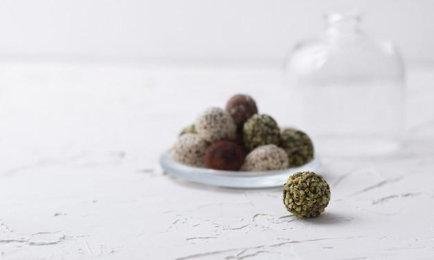 Biologische energiebites met dadels, pompoenpitten, amandel, walnoot en sesam in glazen bakje.