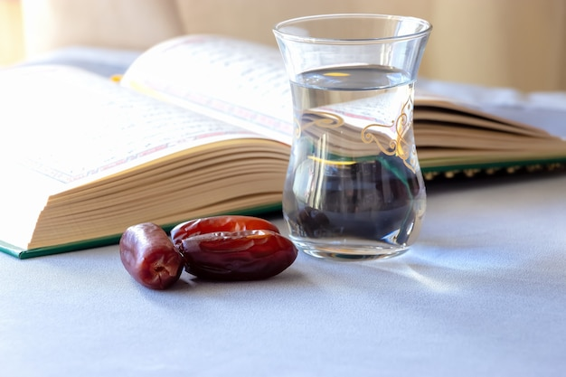 Biologische gedroogde dadels kopje water en boek heilige maand ramadan concept selectieve focus kopieer ruimte