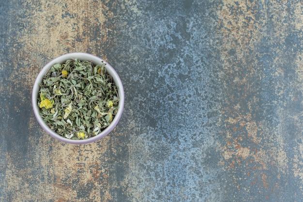 Biologische gedroogde theeblaadjes in witte kom.