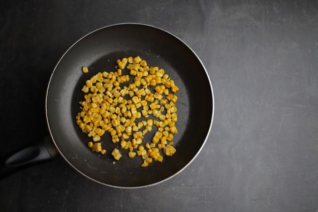 Biologische gegrilde maïs in een koekenpan op grijze achtergrond