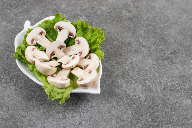 Biologische gehakte champignons met sla op witte plaat.