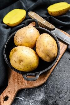 Biologische gele aardappelen in een pan. zwarte achtergrond. bovenaanzicht.
