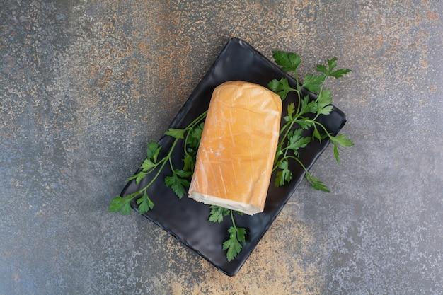 Biologische gele kaas op zwarte plaat met koriander