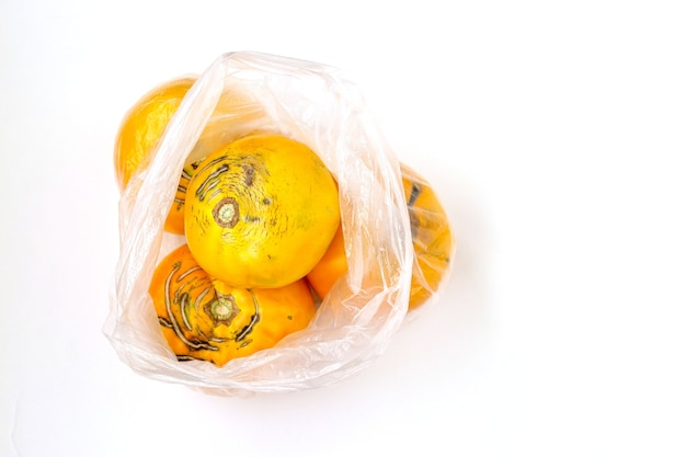 Biologische gele tomaten in plastic zak op een witte achtergrond. gebruik en verkoop van groenten in plastic zakken tijdens een pandemie.