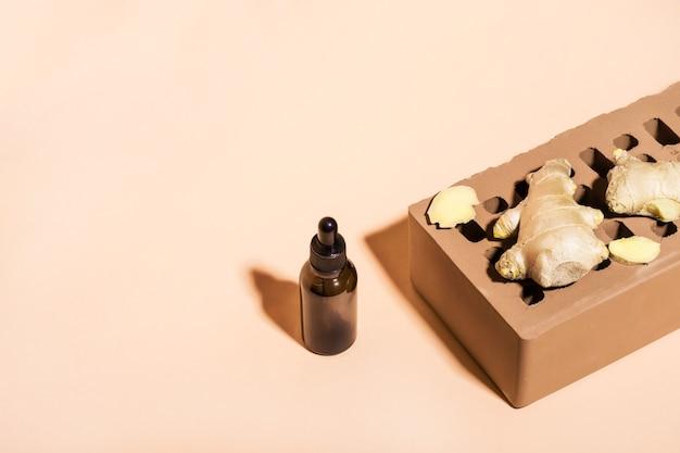 Biologische gember etherische olie in donkere glazen fles, gemberwortel en baksteen op beige achtergrond. isometrische weergave, kopieer ruimte.