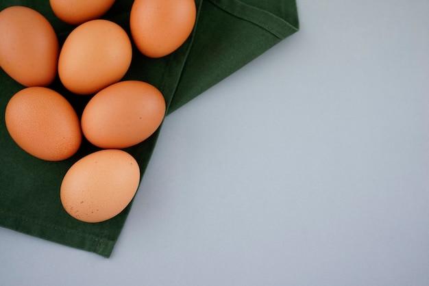 Biologische gespikkelde bruine eieren op groene theedoek servet met kopie ruimte op grijze abstracte achtergrond