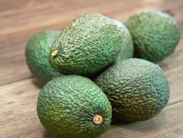 Biologische groene avocado gerangschikt op houten oppervlak.