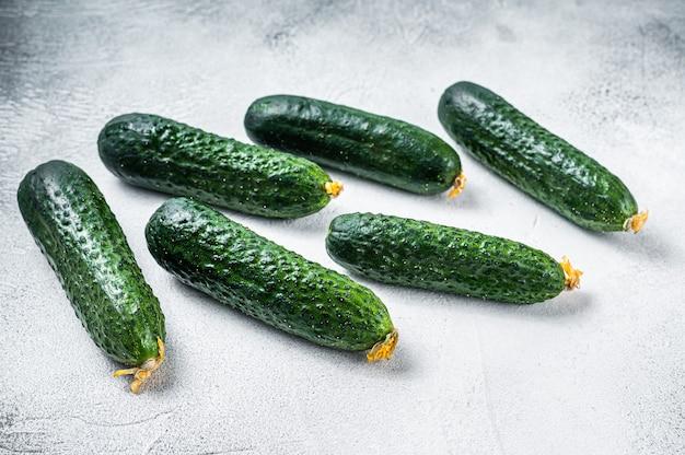 Biologische groene komkommers op een keukentafel. witte achtergrond. bovenaanzicht.