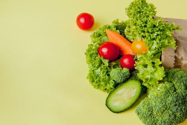 Biologische groenten broccoli komkommers paprika appels in bruin papier
