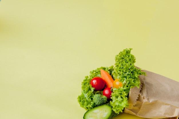 Biologische groenten broccoli komkommers paprika appels in pakpapier kraft kruidenier zak op geel. gezonde voeding dieetvezel veganistisch plastic gratis. poster banner