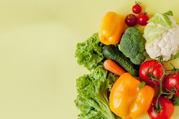 Biologische groenten broccoli komkommers paprika appels in pakpapier kraft kruidenier zak op geel