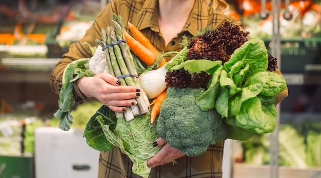 Biologische groenten close-up. mooie jonge vrouw die in een supermarkt winkelt en verse biologische groenten koopt