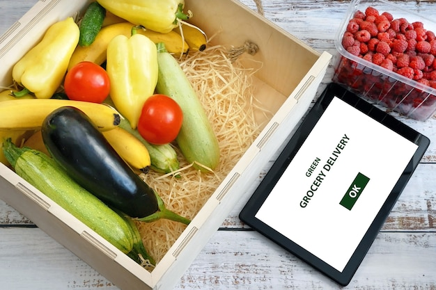 Biologische groenten en fruit in houten kist en tablet-pc