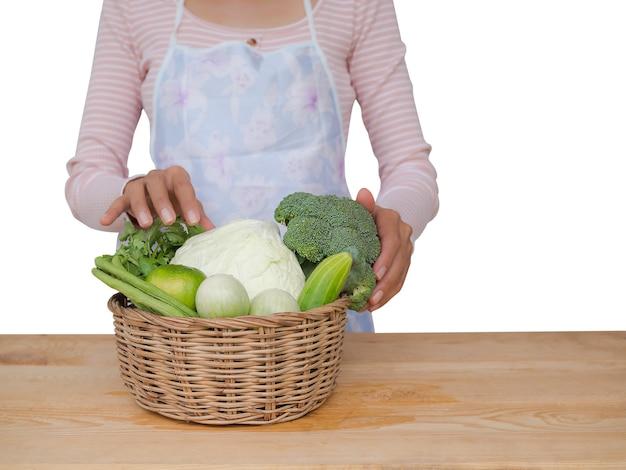 Biologische groenten in de mand met vrouw. limoen, kousenband, aubergine, komkommer, kool, broccoli.