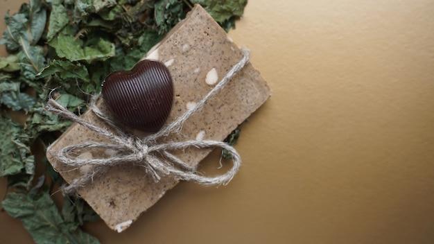 Biologische handgemaakte zeep gemaakt van veldkruiden. zeep in een touw met droog gras en chocoladesuikergoed op een gouden ondergrond