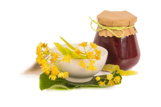 Biologische honing in glazen pot met linden bloemen, geïsoleerd
