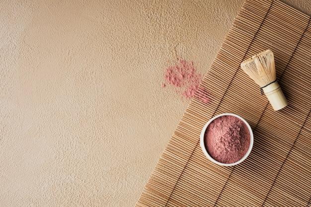 Biologische kleurpoeder thee matcha met japanse gereedschappen bamboe garde op beige ondergrond