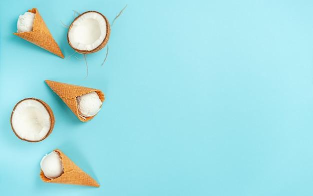 Biologische kokosijs kegels op heldere blauwe achtergrond. plat leggen, ruimte kopiëren.