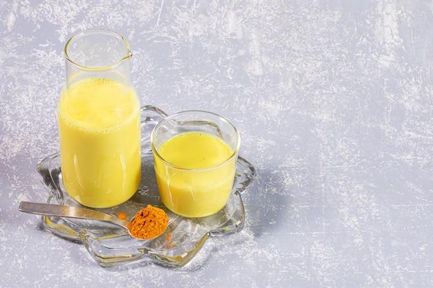Biologische kurkumamelk. fles en glas met gouden melk op dacht transparante plaat op lichtgrijze achtergrond.