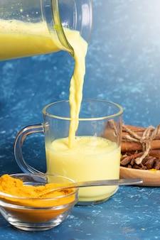 Biologische kurkumamelk. gouden melkstroom stroomt in glas van karaf en ingrediënten op blauwe achtergrond.