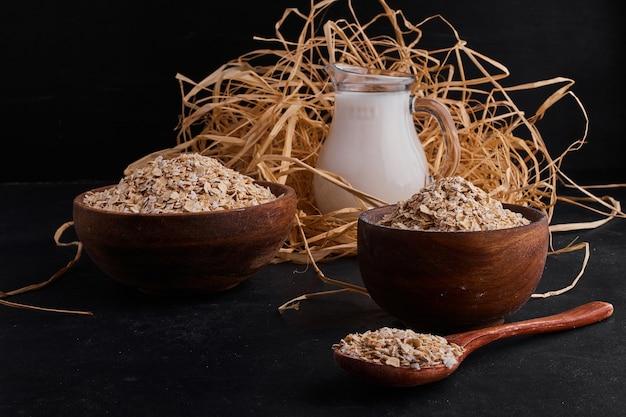 Biologische mueslies in houten bekers en lepel met een potje melk.