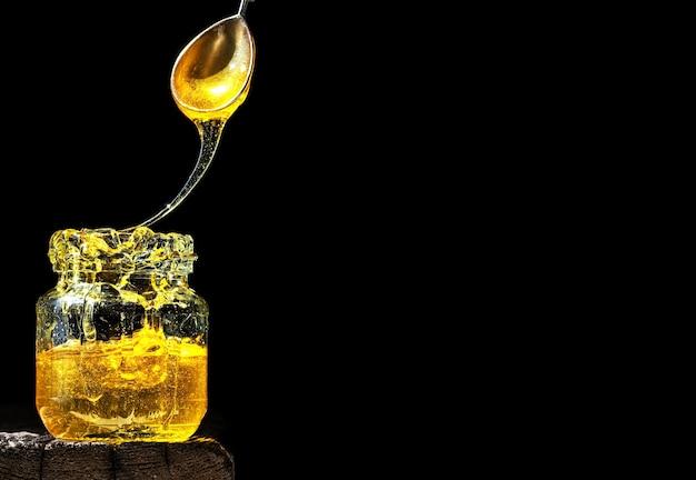 Biologische natuurlijke honing, verlicht door fel zonlicht, in een glazen pot, op een zwarte ondergrond