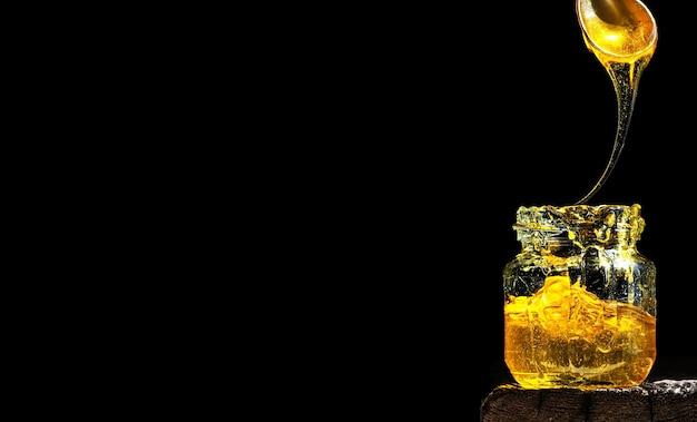 Biologische natuurlijke honing, verlicht door fel zonlicht, in een glazen pot