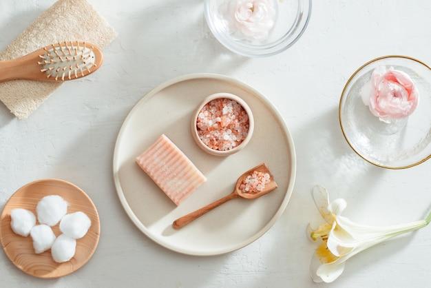 Biologische natuurlijke spa- en huidverzorgingsingrediënten met natuurlijke zeep, bloemen, oliefles, handdoek, zout